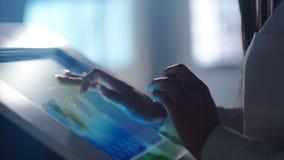 Primo piano dello schermo moderno commovente delle mani nell'ufficio di ciao-tecnologia o nel laboratorio del software stock footage