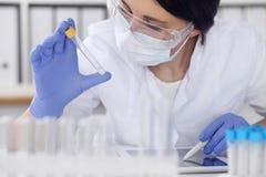 Primo piano dello scienziato femminile professionista in occhiali protettivi che fanno esperimento con i reagenti in laboratorio Fotografia Stock