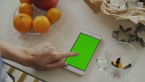 Primo piano dello smartphone di lettura rapida della mano del ` s della donna con lo schermo verde sul tavolo da cucina a casa archivi video