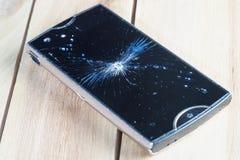 Primo piano dello smartphone mobile con lo schermo rotto su fondo di legno Immagine Stock