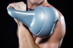 Primo piano dello sportivo senza camicia che risolve con il kettlebell Immagine Stock