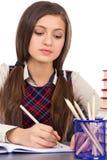 Primo piano dello studente che si siede al suo scrittorio concentrato e che fa h Immagini Stock