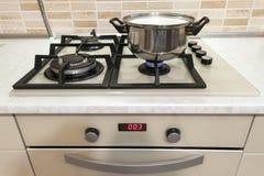 Primo piano di acciaio inossidabile che cucina vaso sulla stufa di gas in contempo Immagine Stock