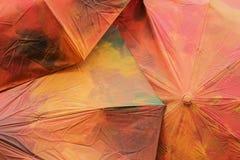 Primo piano di alcuni ombrelli dipinti nei colori d'annata rosso-arancio di autunno Fondo di caduta stagioni Fotografie Stock