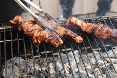 Primo piano di alcuni spiedi della carne che sono grigliati in un barbecue Immagini Stock Libere da Diritti