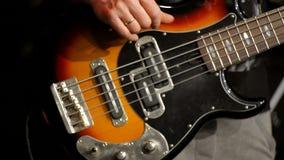 Primo piano di Bass Player Making Music con Bass Guitar al concerto della banda rock stock footage