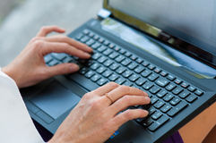 Primo piano di battitura a macchina delle mani a macchina femminili sulla tastiera Fotografia Stock
