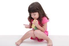 Bambina che beve da un contenitore di succo immagine stock libera da diritti