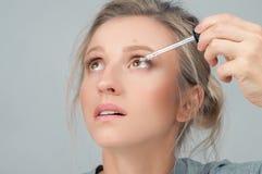 Primo piano di bella donna che applica il collirio nei suoi occhi fotografia stock