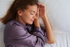 Primo piano di bella donna serena che dorme dal suo lato con Han Immagine Stock