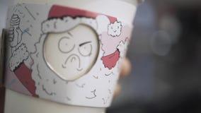 Primo piano di bella e tazza di caffè originale della schiuma di stirolo con i fronti divertenti nella mano di barista azione Caf archivi video