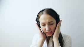 Primo piano di bella giovane donna che ascolta la musica in cuffie archivi video