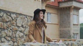 Primo piano di bella giovane donna con un cappello che sta su un balcone di pietra, ondeggiando la sua mano, parlante con sconosc archivi video