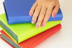 Primo piano di bella progettazione rosa del chiodo alla mano femminile alla pila di fotografie stock libere da diritti