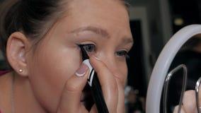 Primo piano di bella ragazza che fa trucco, frecce di tiraggio sopra l'occhio, eye-liner video d archivio