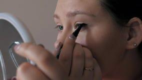 Primo piano di bella ragazza che fa trucco, frecce di tiraggio sopra l'occhio, eye-liner archivi video