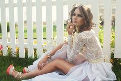 Primo piano di bella ragazza con trucco scuro in vestito bianco lungo Fotografia Stock