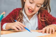 Primo piano di bella ragazza su un fondo grigio Prendendo la a corregga gode del processo del disegno Sulla tavola immagini stock