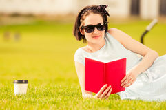 Primo piano di bella seduta femminile allegra con il libro su erba Fotografia Stock Libera da Diritti