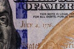 Primo piano di Ben Franklin e la data indipendenza del 4 luglio 1776 su cento banconote in dollari per fondo VI Immagine Stock