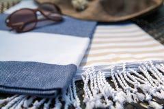 Primo piano di bianco, asciugamano turco blu e beige, occhiali da sole e cappello di paglia sulla chaise-lounge del rattan immagine stock