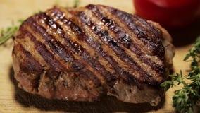 Primo piano di bistecca arrostita sulla superficie di legno stock footage