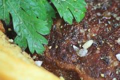 Primo piano di bistecca con le patatine fritte ed il prezzemolo Fotografia Stock