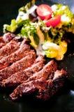 Primo piano di bistecca cotta con insalata fotografia stock