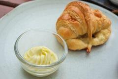 Primo piano di burro e del croissant fresco Immagine Stock