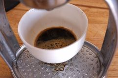 Primo piano di caffè espresso che versa dalla macchina del caffè Mano dell'uomo con caffè fotografia stock