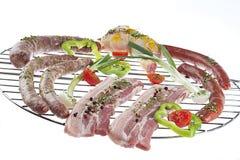 Primo piano di carne fresca e delle salsiccie sulla griglia del barbecue Fotografia Stock