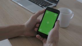 Primo piano di contatto maschio delle mani dello smartphone alla tavola del posto di lavoro Chiave verde di intensità dello scher stock footage