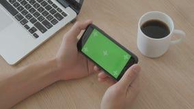 Primo piano di contatto maschio delle mani dello smartphone alla tavola del posto di lavoro Chiave verde di intensità dello scher video d archivio