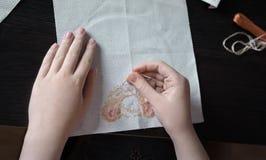 primo piano di cucitura trasversale della mano del bambino sui precedenti la tavola scura Immagine Stock