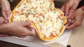 Primo piano di diverse mani della gente che prendono le fette della pizza dalla scatola stock footage