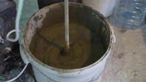 Primo piano di fabbricazione del mortaio in secchio al cantiere stock footage