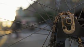 Primo piano di filatura della ruota di bicicletta al tramonto della città Trasporto urbano ecologico stock footage