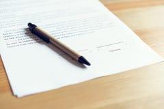 Primo piano di firma un accordo e della penna della documentazione sulla tavola fotografia stock libera da diritti