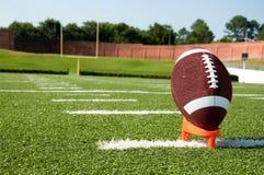 Primo piano di football americano sul T sul campo Fotografia Stock