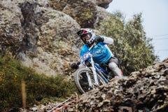 Primo piano di giovane atleta del cavaliere sulla bicicletta su una roccia Fotografie Stock Libere da Diritti