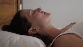 Primo piano di giovane bella donna allegra che si trova dal lato nel letto, mette la sua testa sulla macro del primo piano del cu stock footage