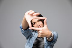 Primo piano di giovane bella donna castana che fa struttura con le sue dita, sopra fondo grigio Fotografie Stock