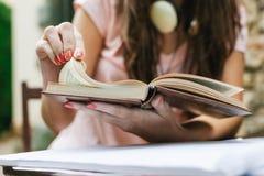 Primo piano di giovane bella seduta femminile esterna e di studio duro Fotografie Stock