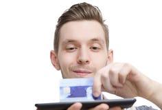 Primo piano di giovane carta di credito della tenuta del tipo su una compressa fotografie stock