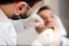 Primo piano di giovane dentista maschio che tiene una siringa, dante anestetico ad un paziente maschio maturo Vista dell'angolo a fotografia stock