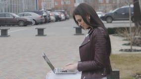 Primo piano di giovane donna di affari attraente che per mezzo del computer portatile su una rottura all'aperto stock footage