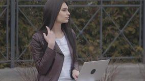 Primo piano di giovane donna di affari attraente che per mezzo del computer portatile su una rottura all'aperto video d archivio
