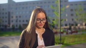 Primo piano di giovane donna di affari o studentessa attraente professionista, donna che usando il suo esterno del computer porta video d archivio