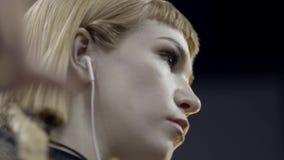 Primo piano di giovane donna attraente che ascolta la musica con le cuffie azione Bello ascolto artistico della giovane donna archivi video