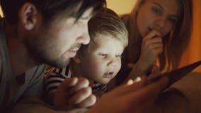 Primo piano di giovane famiglia felice che si trova a letto a casa mentre ragazzino che impara giocare prima il computer digitale immagini stock libere da diritti